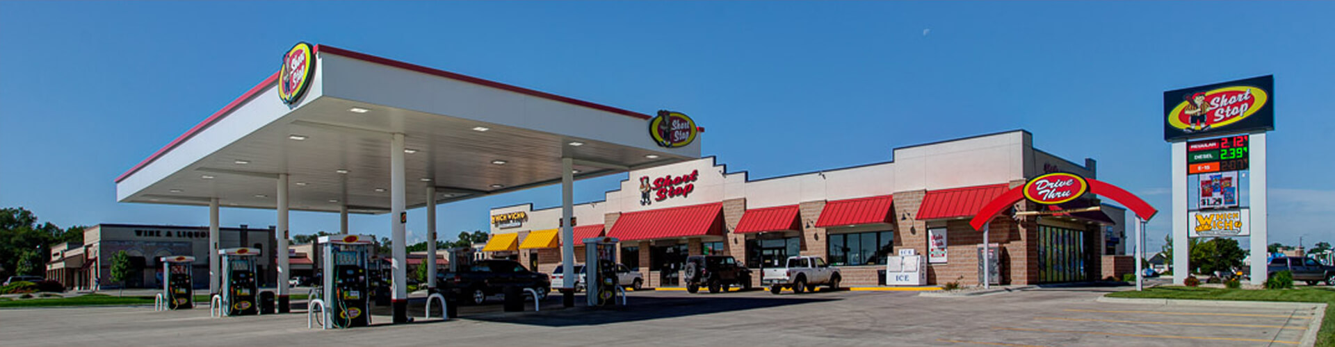 view of short stop convenience store and gas pumps on a bright sunny with a cloudless blue sky